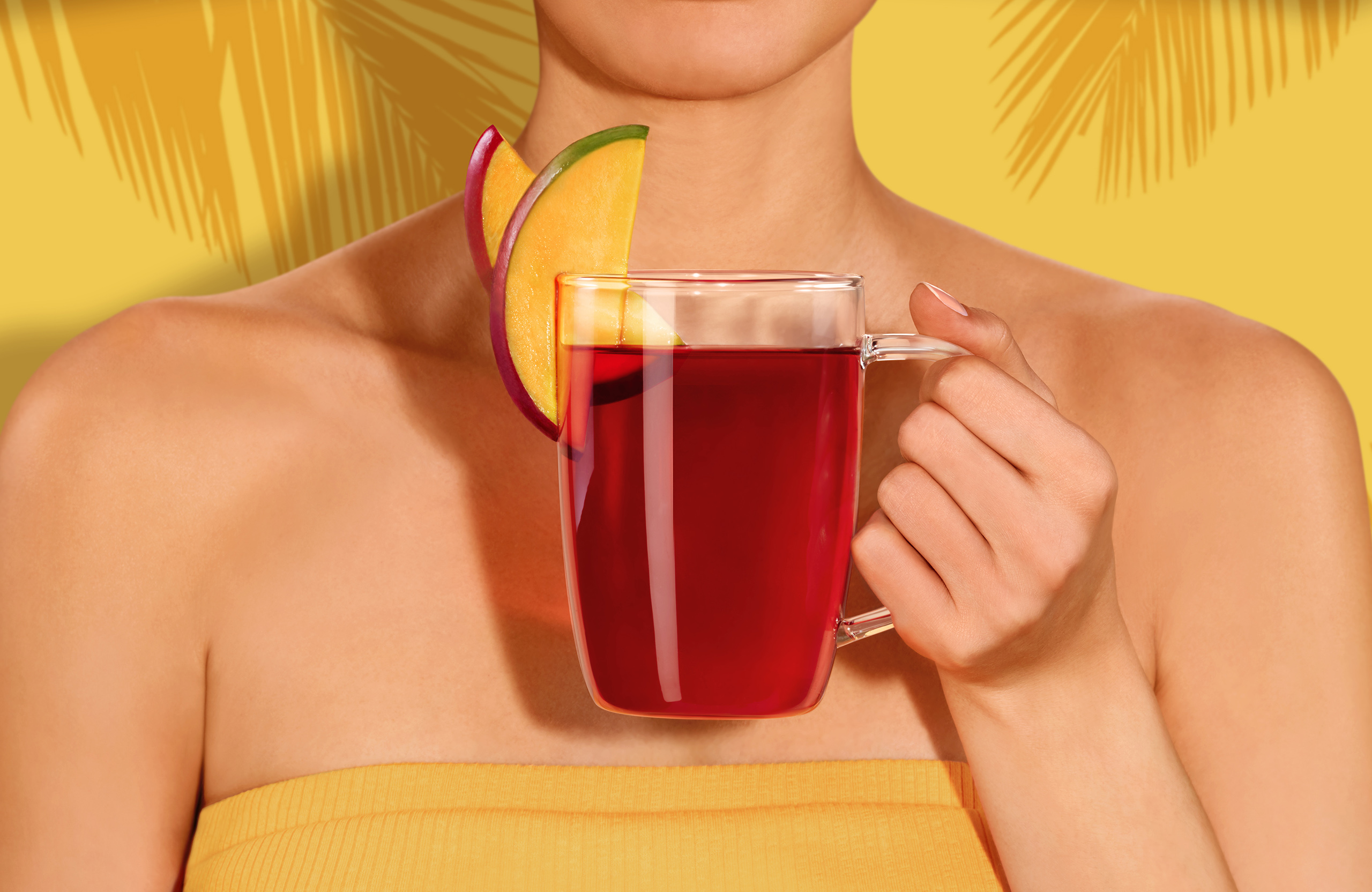 Commercial photography for Kusmi Tea of a girl with a red beach hat and a yellow dress holding a mug of tea Aquaexotica with slices of mango with a palm tree yellow background retouched by Maria Queralt